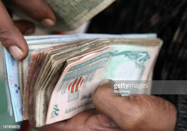 A vender counts bank notes at a market in Dhaka Bangladesh on Monday Jan 9 2012 Bangladesh's central bank this month raised interest rates for the...