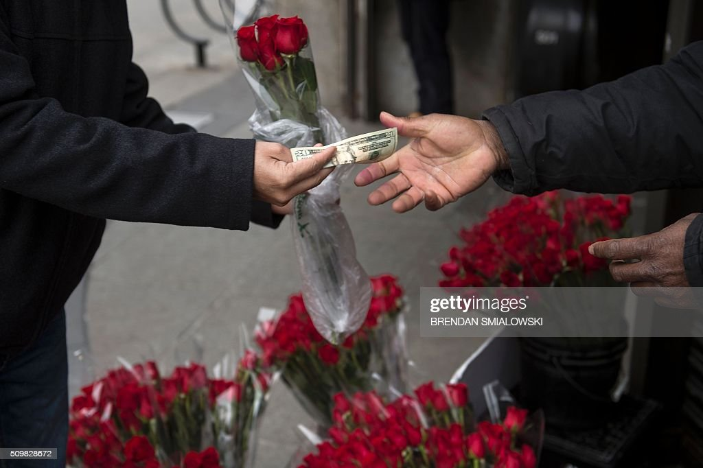 A vender sell roses to a passerby on February 12, 2016 in Washington, DC. Valentine's Day is observed on February 14. / AFP / Brendan Smialowski