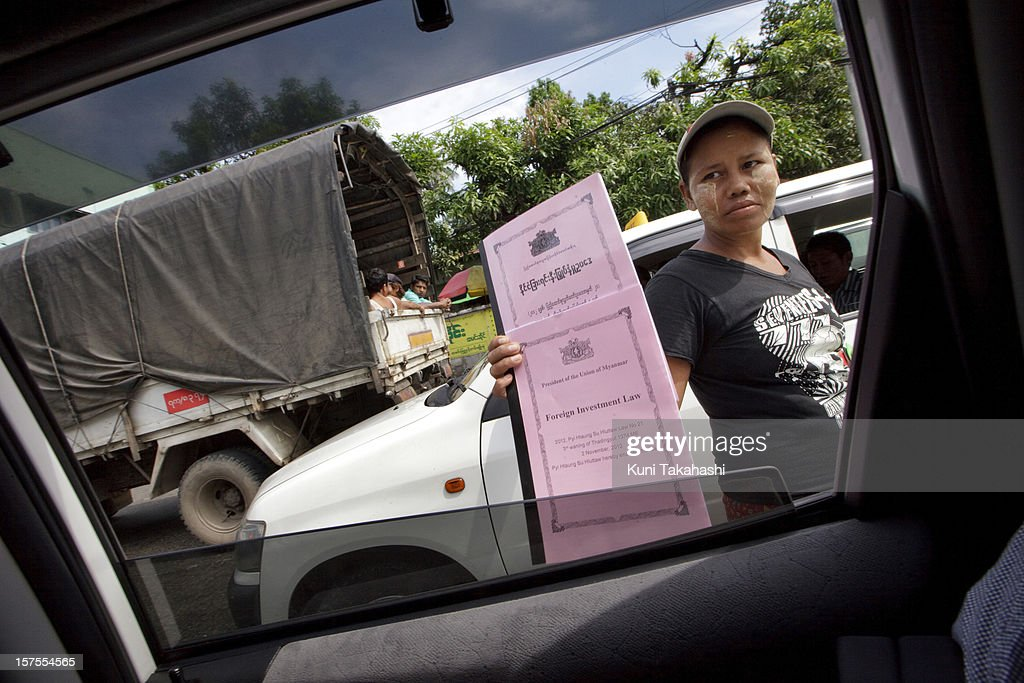A vender sells Foreign Investment Low booklet at intersection on November 14, 2012 in Yangon, Myanmar. Myanmar's economy is predicted to grow by over 6.0% next year on the back of commodity exports and a increase in foreign investment.