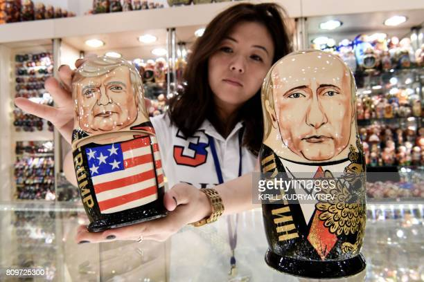 A vender shows traditional Russian wooden nesting dolls called Matryoshka dolls depicting US President Donald Trump and Russia's President Vladimir...