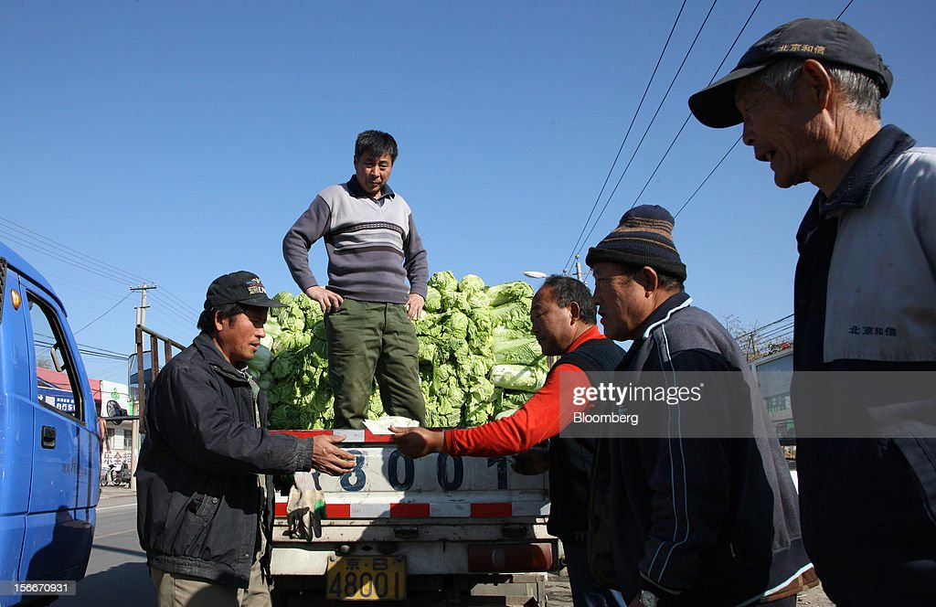 Venders, left and second from left, sell Chinese cabbages on a street in Pinggu, on the outskirts of Beijing, China, on Saturday, Nov. 17, 2012. China's gross domestic product slowed to 7.4 percent in the July-September period from a year earlier, the weakest in three years. Photographer: Tomohiro Ohsumi/Bloomberg via Getty Images