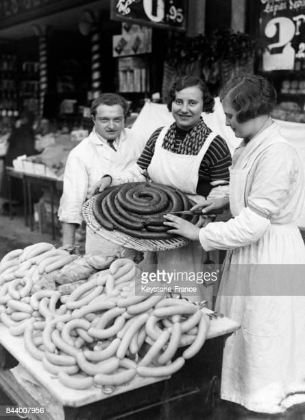 Vendeuse présentant du boudin noir audessus d'un étal de boudin blanc à Paris France en décembre 1932