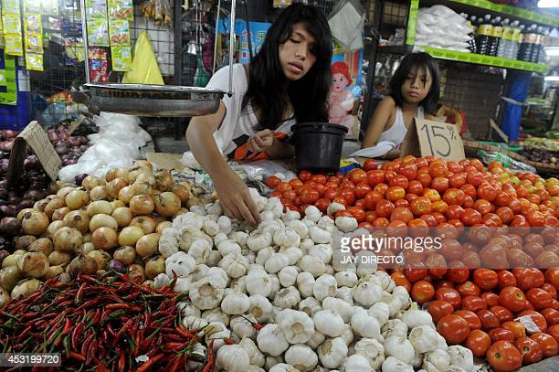 A vendo selling garlic at a market in Manila on August 5 2014 Philippine inflation shot up to a nearly threeyear high of 49 percent in July the...