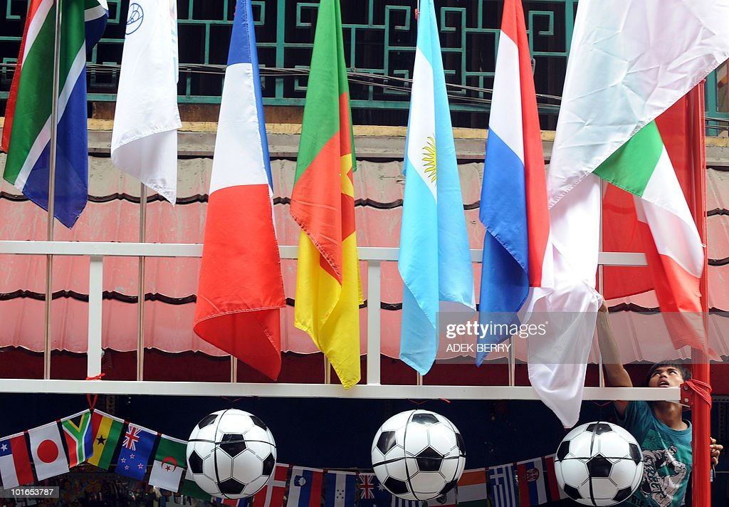 A vendor adjusts a flag as balls and flags of participating countries in the 2010 World Cup football tournament at a market in Jakarta on June 6, 2010.