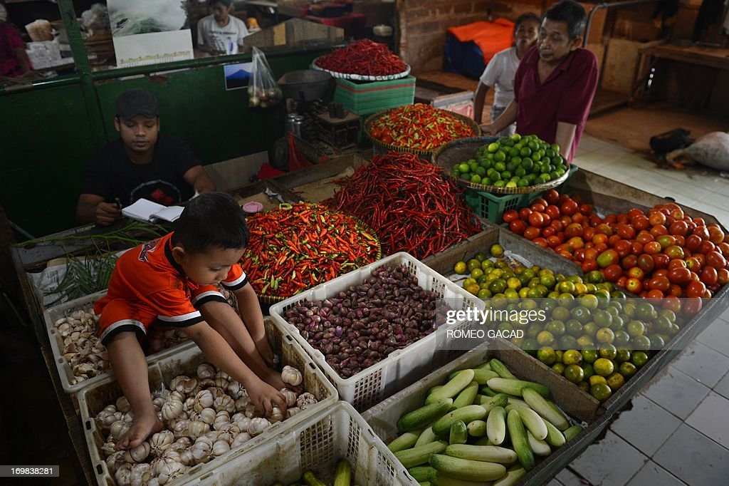A vendor and his son attend to vegetable stall at a market in Jakarta on June 3, 2013. Indonesia's inflation rate unexpectedly slowed to 5.47 percent year-on-year in May due to lower food prices, official data showed June 3. Inflation was now back within the government's 2013 inflation target range of 3.5-5.5 percent, according to the central statistics agency, after slowing from 5.57 percent in April.