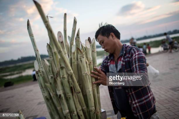 A vendor arranges a bunch of sugarcane on a promenade along the Mekong river in Vientiane Laos on Thursday Nov 2 2017 Located in the Mekong region...