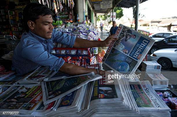 A vendor arranges a newspaper with reports about the missing Malaysia Airlines Boeing 777200 plane in Kuala Lumpur on March 11 2014 Malaysia has...