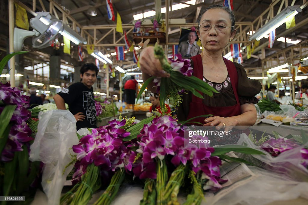 A vendor arranges bouquets of orchids for sale at the Pak Khlong market in Bangkok, Thailand, on Sunday, Aug. 18, 2013. Thai economic growth slowed for a second quarter as exports cooled and local demand weakened, with rising household debt restricting the scope for monetary easing. Photographer: Dario Pignatelli/Bloomberg via Getty Images