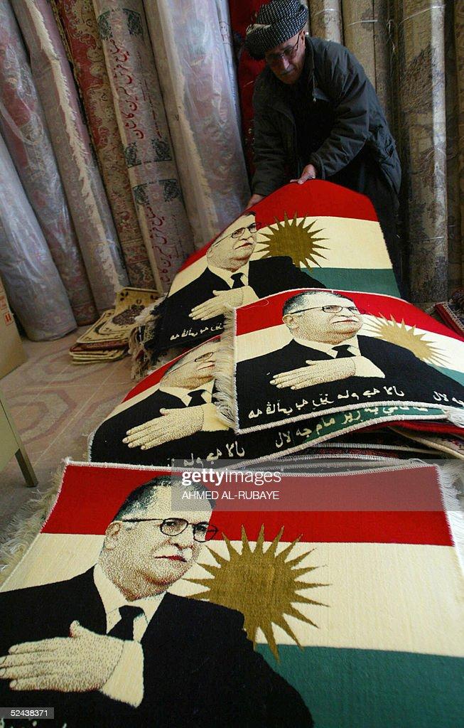 A vendor arranges carpets depicting the image of Kurdish leader Jalal Talabani in the city of Sulaimaniyah 330 kilometers north of Baghdad 17 March...