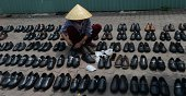A vendor arranges cheap Chinese shoes for sale on the pavement in Hanoi on August 21 2014 Vietnamese Deputy Prime Minister Nguyen Xuan Phuc quoted by...