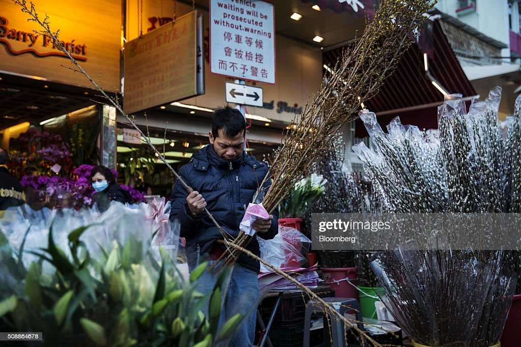 A vendor arranges flowers for sale for the Lunar New Year at a flower market in the Mong Kok district of Hong Kong, China, on Sunday, Feb 7, 2016. The city's financial markets will close on Feb. 8 for the Lunar New Year holidays and resume trading on Feb. 11. Photographer: Billy H.C. Kwok/Bloomberg via Getty Images