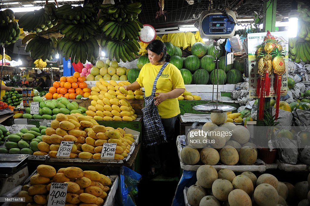 A vendor arranges fruits for sale at a market in Manila on March 27, 2013. The Philippines won its first investment-grade credit rating on March 27 in a move President Benigno Aquino hailed as proof his country was no longer Asia's economic backwater. AFP PHOTO/NOEL CELIS