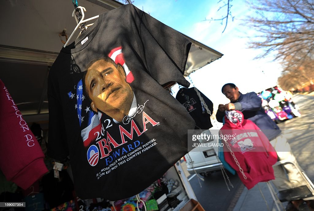 A vendor arranges his roadside souvenir stall displaying T-shirts with US President Barack Obama's pictures in Washington, DC, on January 5, 2013. Preparations are underway for Obama's second inauguration which will take place with a public ceremonial oath of office on January 21, 2013. AFP PHOTO/Jewel Samad