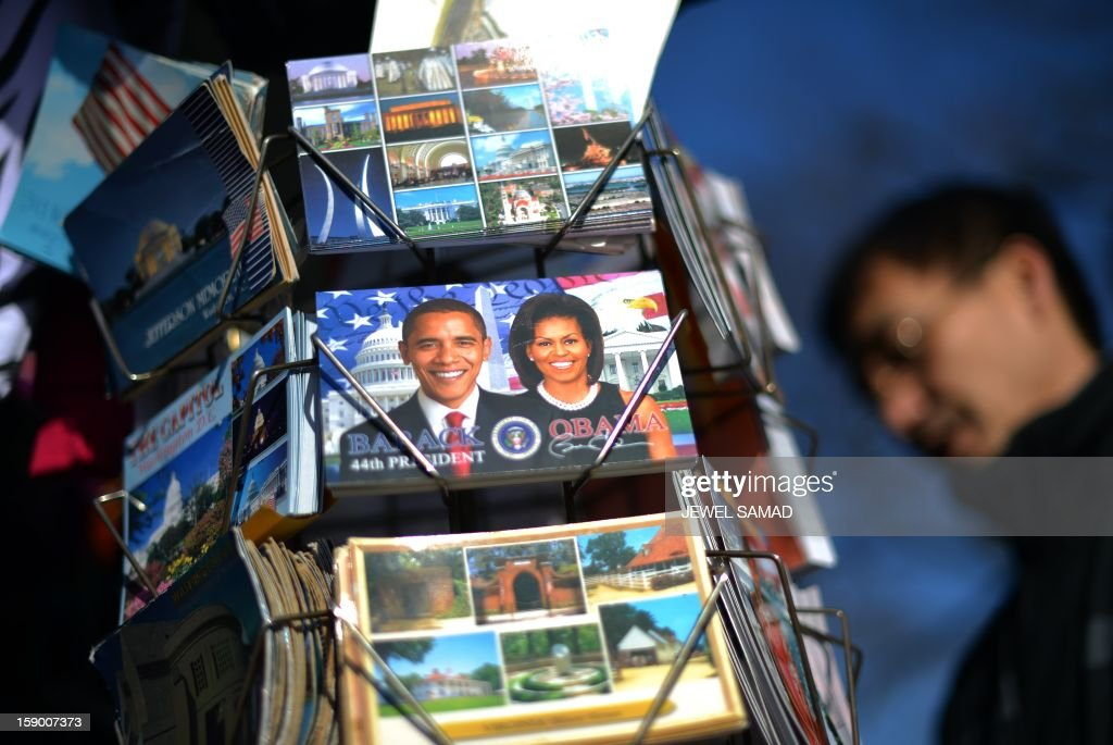 A vendor arranges his roadside souvenir stall with postcards featuring pictures of US President Barack Obama and First Lady Michelle Obama in Washington on January 5, 2013. Preparations are underway for Obama's second inauguration which will take place with a public ceremonial oath of office on January 21. AFP PHOTO/Jewel Samad