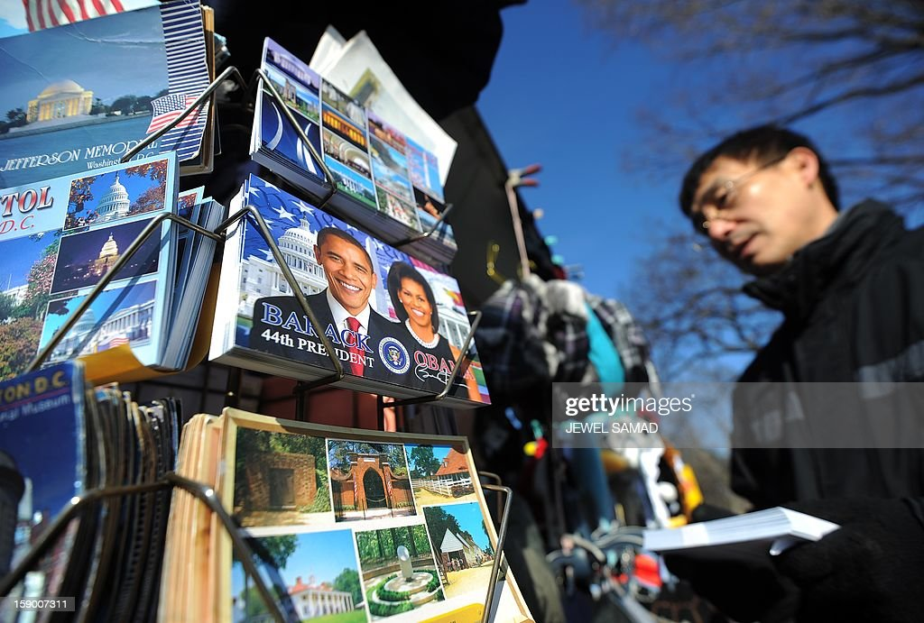A vendor arranges his roadside stall with postcards of US President Barack Obama in Washington on January 5, 2013. Preparations are underway for Obama's second inauguration which will take place with a public ceremonial oath of office on January 21. AFP PHOTO/Jewel Samad