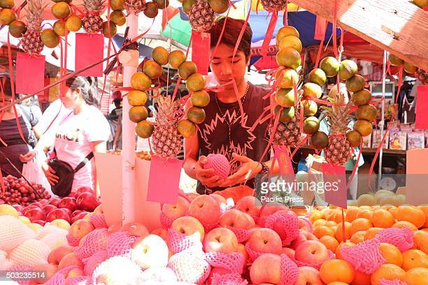 A vendor arranges his round fruit product in Manila as for the celebration of coming new year according to the belief that must prepare 12 round...