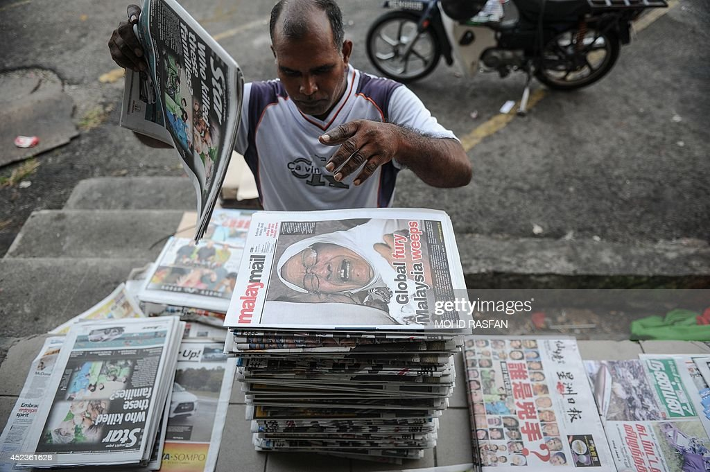 A vendor arranges Malaysian newspapers with reports about the Malaysia Airlines flight MH17 crashed in eastern Ukraine, in Kuala Lumpur on July 19, 2014. Malaysia Airlines Flight MH17 carrying 298 people from Amsterdam to Kuala Lumpur crashed on July 17 in rebel-held east Ukraine, as Kiev said the jet was shot down in a 'terrorist' attack.
