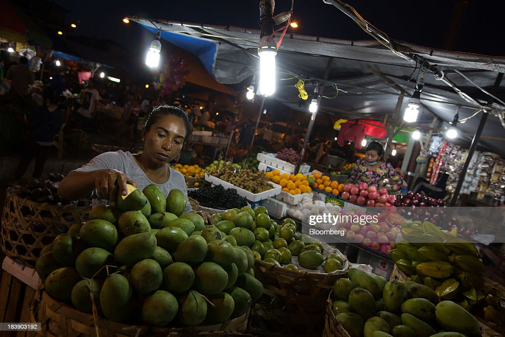 A vendor arranges mangos at a fruit stall in the Pasar Badung market in Denpasar, Bali, Indonesia, on Tuesday, Oct. 8, 2013. Bank Indonesia said it will regulate currency hedging by individuals and companies, including state-owned firms, to help stabilize Asias most-volatile currency. Photographer: SeongJoon Cho/Bloomberg via Getty Images