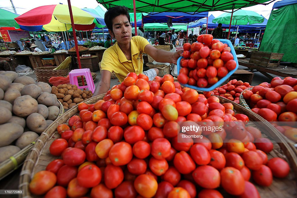 A vendor arranges tomatoes at a market stall in Naypyidaw, Myanmar, on Friday, June 7, 2013. President Thein Sein has allowed more political freedom and loosened economic controls since coming to power two years ago, prompting the U.S. and other nations to ease sanctions. Photographer: Dario Pignatelli/Bloomberg via Getty Images