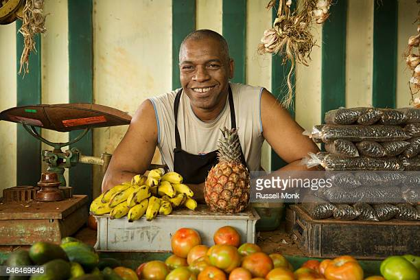 A vendor at a fruit and vegetable market