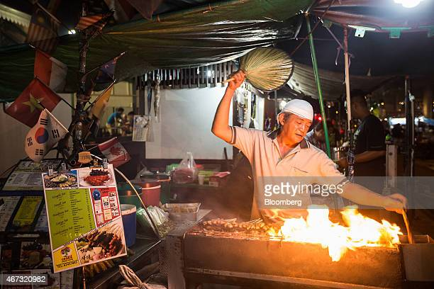 A vendor barbecues satay at the Lau Pa Sat food court in the central business district city of Singapore on Sunday March 22 2015 Lee Kuan Yew who...
