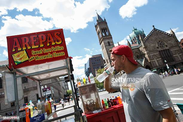 Vendor Bernardo Rosetti drinks water to stay cool at his arepa stand on Copley Square in Boston MA July 26 the sixth day of a heat wave Rosetti...
