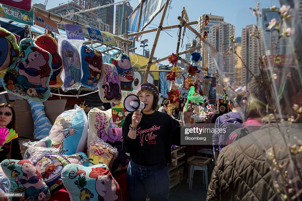 A vendor calls for customers with a megaphone at the Lunar New Year fair in Victoria Park in Hong Kong, China, on Sunday, Feb 7, 2016. The city's financial markets will close on Feb. 8 for the Lunar New Year holidays and resume trading on Feb. 11. Photographer: Billy H.C. Kwok/Bloomberg via Getty Images