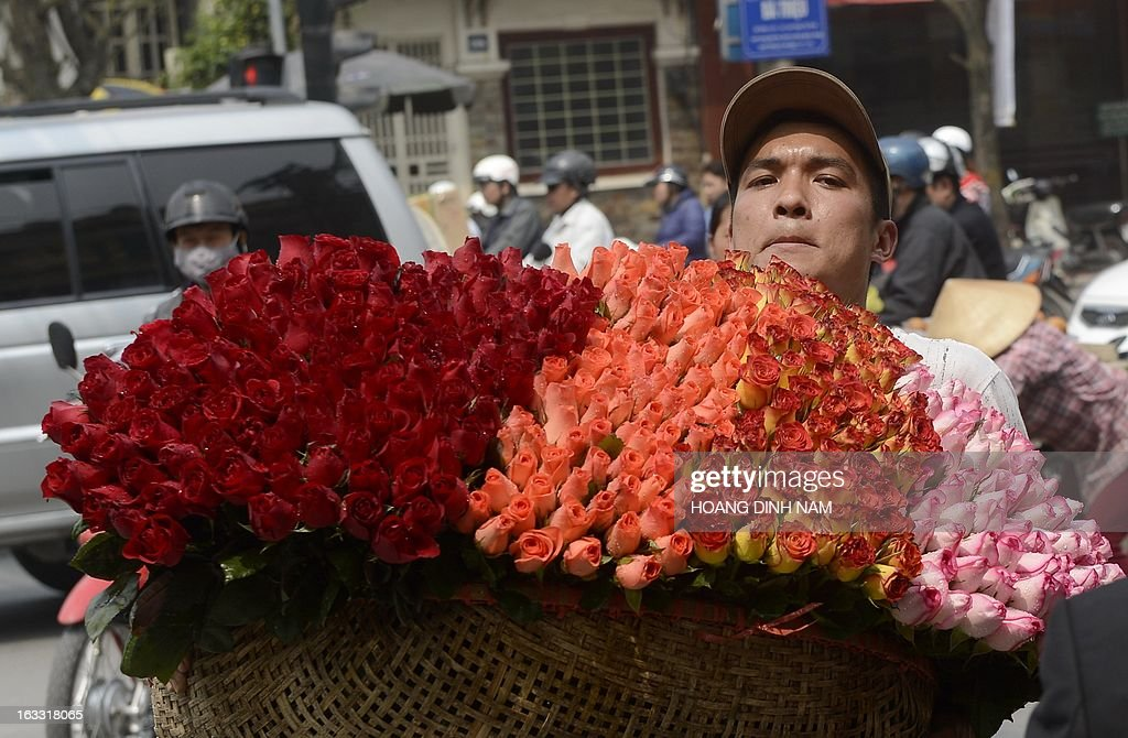 A vendor carries a basket of roses for sale on a street as Vietnamese celebrate the International Women's Day in Hanoi on March 8, 2013. The day is a good business opportunity for florists with a sharp rise of flowers's prices, especially for roses. AFP PHOTO/HOANG DINH Nam