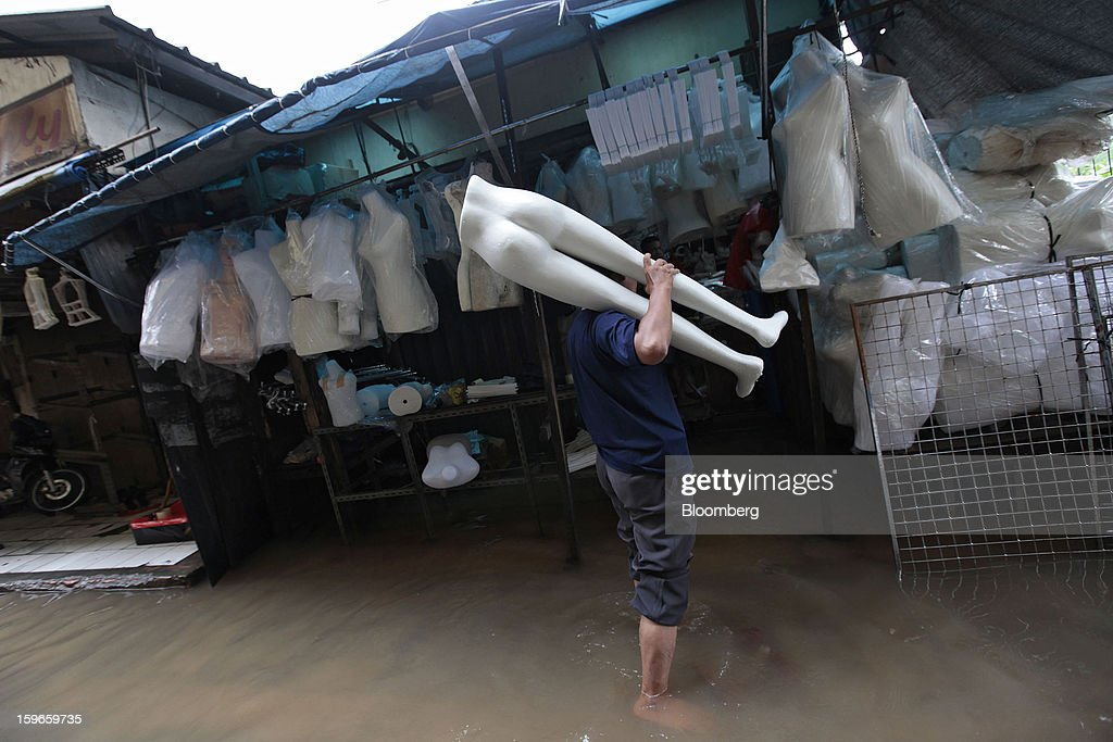 A vendor carries a mannequin through floodwaters at his stall at the Cipulir market in Jakarta, Indonesia, on Friday, Jan. 18, 2013. Indonesia declared a state of emergency in Jakarta as flooding brought traffic to a standstill in the city of 9.6 million people and swamped the offices of President Susilo Bambang Yudhoyono. Photograph by: Dimas Ardian/Bloomberg via Getty Images