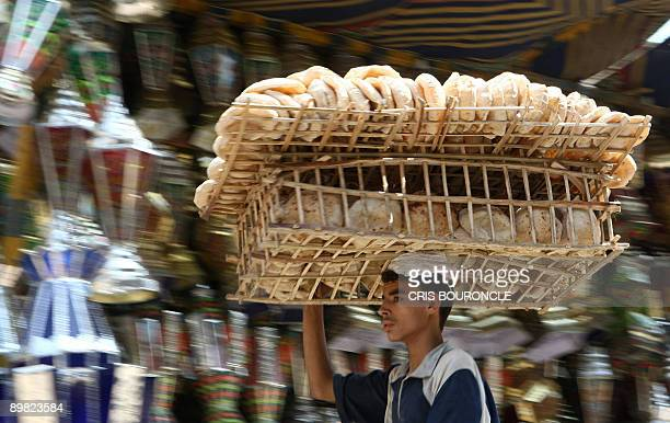 A vendor carries a tray of bread loafs as he rides a bicycle past a stall selling traditional tin lanterns known as Fawanis used by Egyptians to...