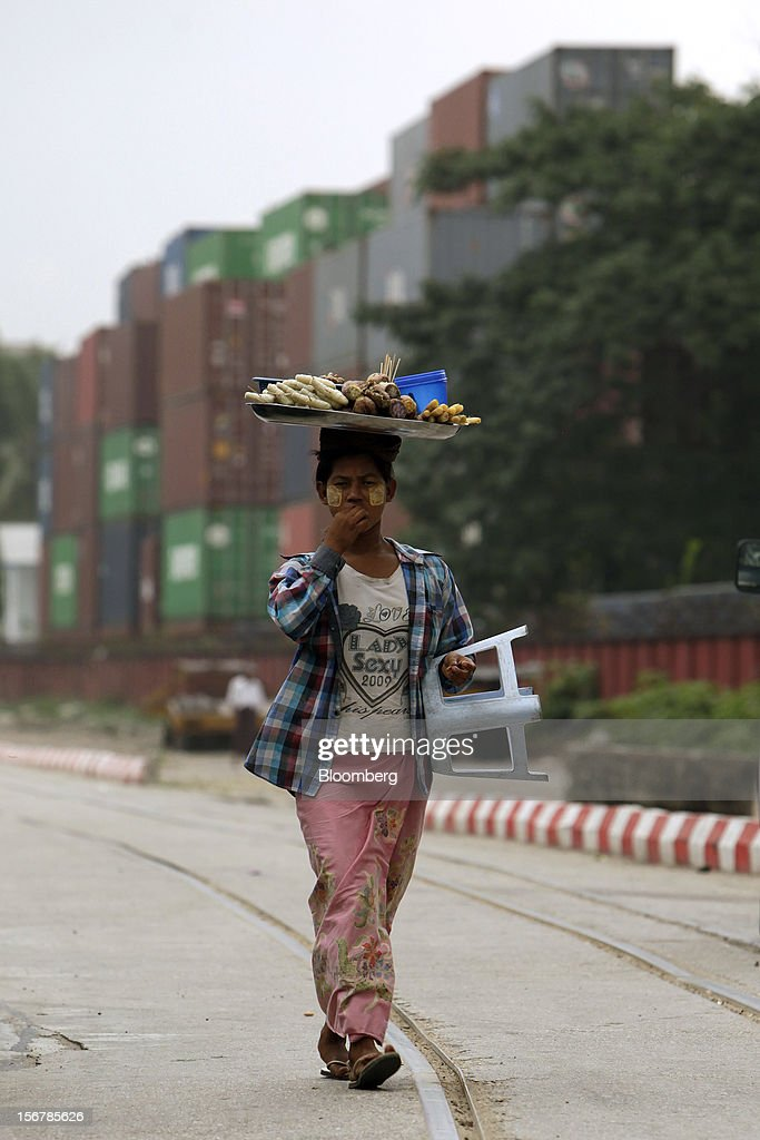 A vendor carries a tray of food on her head as she walks through a shipping container depot in Yangon, Myanmar, on Tuesday, Nov. 20, 2012. Myanmar's growth outlook has improved 'substantially' amid political reforms, which are expected to lead to a large influx of foreign investment, the Organization for Economic Cooperation and Development (OECD) said on Nov. 18. Photographer: Dario Pignatelli/Bloomberg via Getty Images