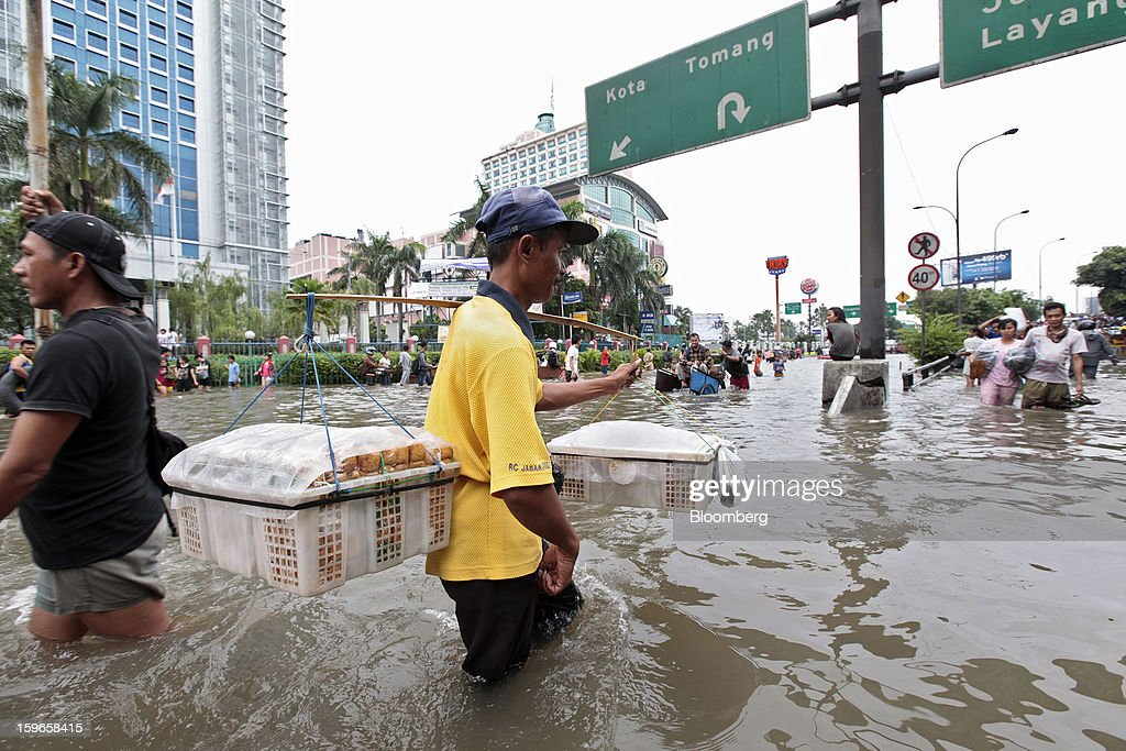 A vendor carries baskets of tofu as he wades through floodwaters in Jakarta, Indonesia, on Friday, Jan. 18, 2013. Indonesia declared a state of emergency in Jakarta as flooding brought traffic to a standstill in the city of 9.6 million people and swamped the offices of President Susilo Bambang Yudhoyono. Photograph by: Dimas Ardian/Bloomberg via Getty Images
