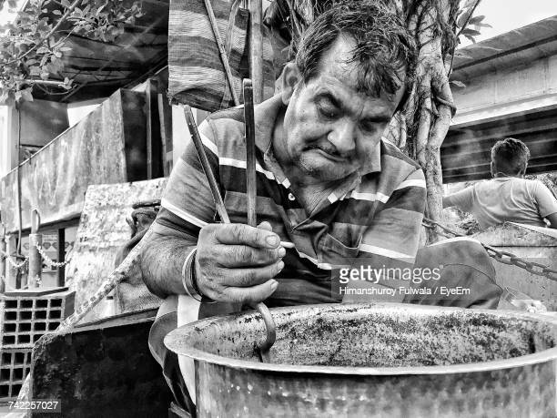 Vendor Carrying Utensil With Serving Tongs At Market Stall
