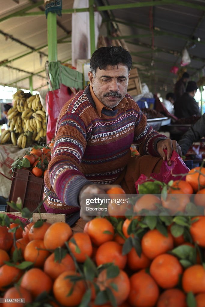 A vendor chooses fruits for sale at a market in Islamabad, Pakistan, on Sunday, Dec. 30, 2012. Pakistan's economy will probably expand 3.5 percent in the 12 months through June, the International Monetary Fund forecast Nov. 29, less than the 4.3 percent predicted by the government. Photographer: Asad Zaidi/Bloomberg via Getty Images