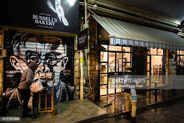 A Vendor closes her store with a graffiti depicting Zionist leader Ze'ev Jabotinsky which was painted the closed shutter of the store at the Mahane...