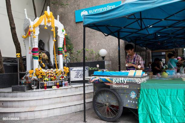A vendor cooks at a food stall next to a Buddhist shrine in the Phaya Thai District of Bangkok Thailand on Wednesday April 5 2017 The central...