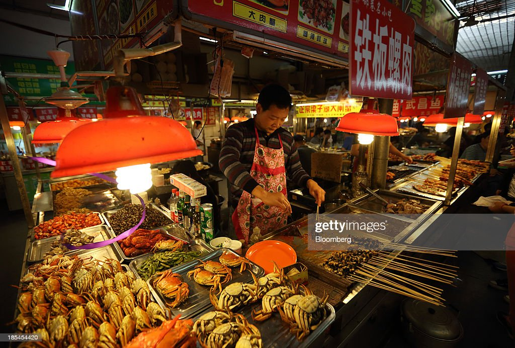 A vendor cooks at a stall in Wuhan, China, on Sunday, Oct. 20, 2013. China's economic expansion accelerated to 7.8 percent in the third quarter from a year earlier, the statistics bureau said Oct. 18, reversing a slowdown that put the government at risk of missing its 7.5 percent growth target for 2013. Photographer: Tomohiro Ohsumi/Bloomberg via Getty Images