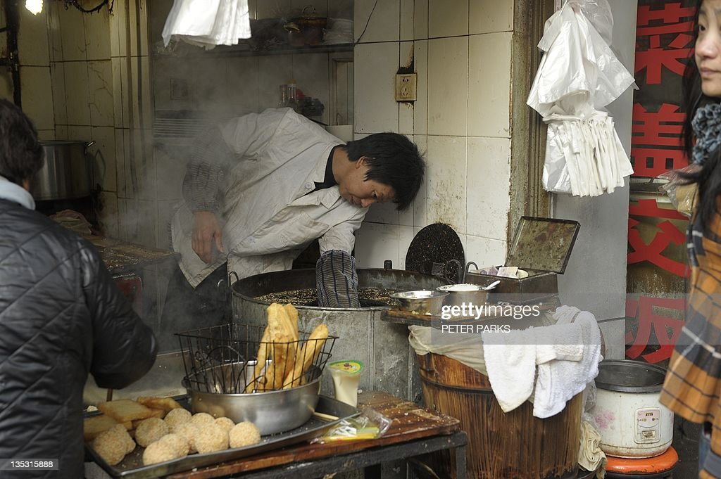 A vendor cooks deep fried bread at a street stall in Shanghai on December 9, 2011. China's consumer prices rose at their slowest pace in over a year in November, data showed December 9, vindicating Beijing's decision to relax credit restrictions to prevent a painful economic slowdown. AFP PHOTO/Peter PARKS