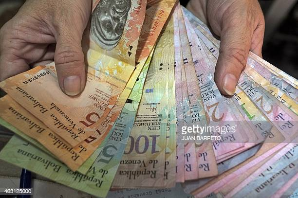 A vendor counts Bolivar notes at her stall in Caracas on February 10 2015 The Venezuelan government confirmed Tuesday the partial release of the...