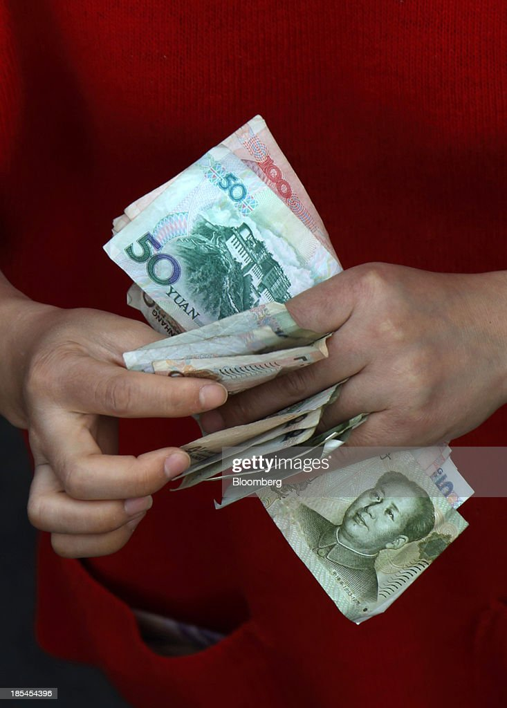 A vendor counts Chinese Yuan notes at her stall in Wuhan, China, on Sunday, Oct. 20, 2013. China's economic expansion accelerated to 7.8 percent in the third quarter from a year earlier, the statistics bureau said Oct. 18, reversing a slowdown that put the government at risk of missing its 7.5 percent growth target for 2013. Photographer: Tomohiro Ohsumi/Bloomberg via Getty Images