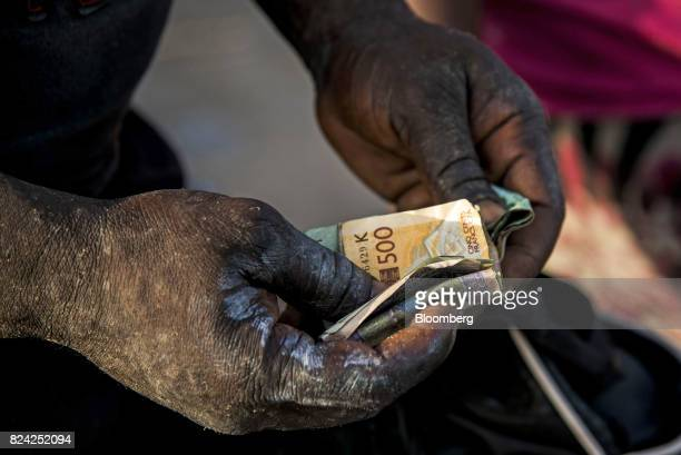 A vendor counts West African CFA franc currency banknotes at the Soumbedioune fish market in Dakar Senegal on Friday July 28 2017 Senegalese voters...