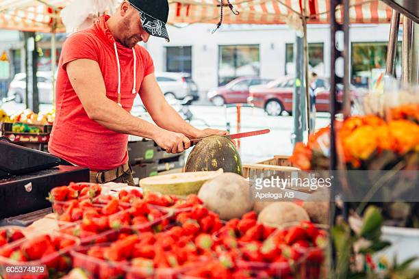 Vendor cutting watermelon at fruit stall in market