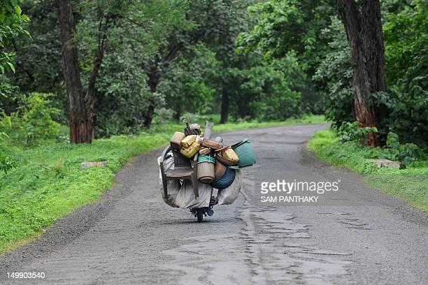 A vendor dealing in discarded and recycleable items drives down a road on his motorcycle in Navapur India's Maharashtra state on August 5 2012 Indian...
