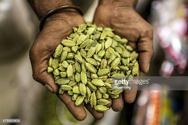 A vendor displays a handful of green cardamom for a photograph at a spice store in Ernakulam Kerala India on Thursday May 28 2015 While consumerprice...