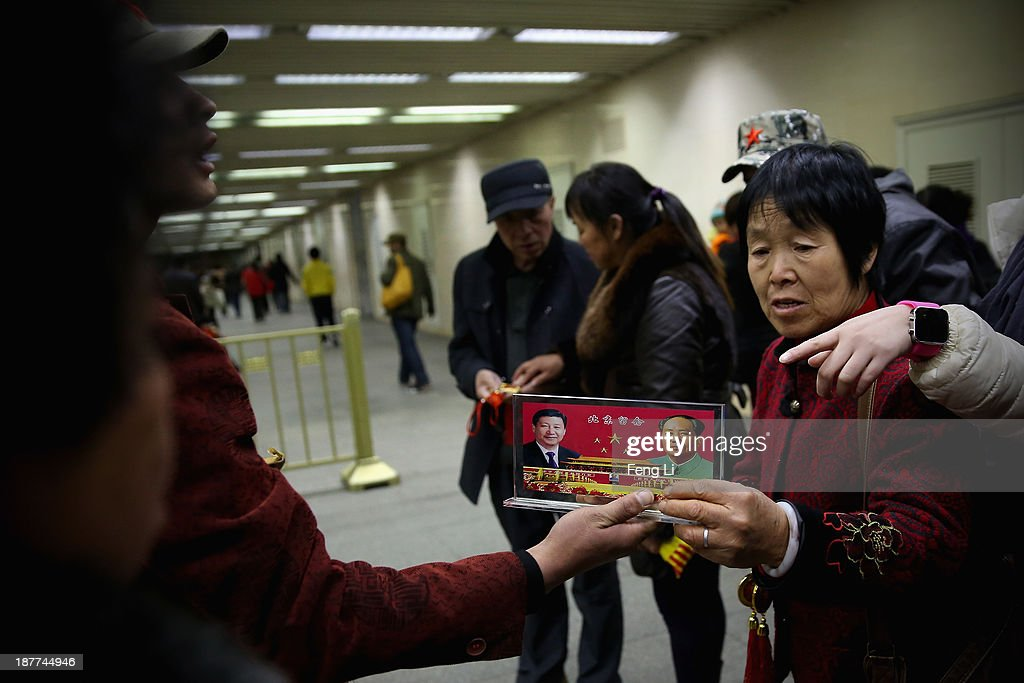 A vendor displays a souvenir with pictures of Chinese President Xi Jinping (Left) and the late Chinese Chairman Mao Zedong (Right) to visitors at the underpass outside the Great Hall of the People where the Communist Party's 205-member Central Committee gathered for its third annual plenum on November 12, 2013 in Beijing, China. The 18th Central Committee of the Communist Party of China (CPC) approved a decision on 'major issues concerning comprehensively deepening reforms' at the close of the Third Plenary Session of the 18th CPC Central Committee on Tuesday.