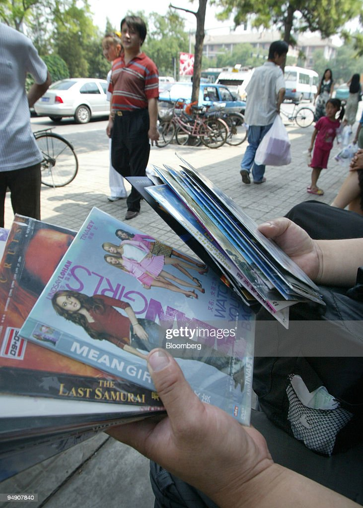 A vendor displays pirated DVDs of recently released films for sale on the street in Beijing China Wednesday June 23 2004
