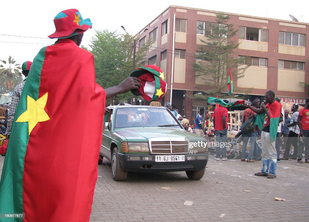 A vendor dressed with Burkina Faso's Flag sells caps featuring Burkina Faso's symbols on February 8, 2013 in Ouagadougou few days before the 2013 Africa Cup of Nations football final match Burkina Faso vs Nigeria.
