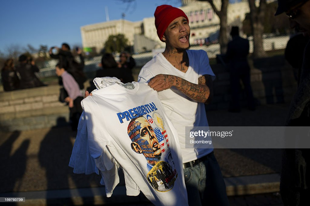 Vendor Dwayne Quattlebaum displays a U.S. President <a gi-track='captionPersonalityLinkClicked' href=/galleries/search?phrase=Barack+Obama&family=editorial&specificpeople=203260 ng-click='$event.stopPropagation()'>Barack Obama</a> t-shirt for sale ahead of the presidential inauguration in Washington, D.C., U.S., on Sunday, Jan. 20, 2013. As he enters his second term Obama has shed the aura of a hopeful consensus builder determined to break partisan gridlock and adopted a more confrontational stance with Republicans. Photographer: Victor J. Blue/Bloomberg via Getty Images