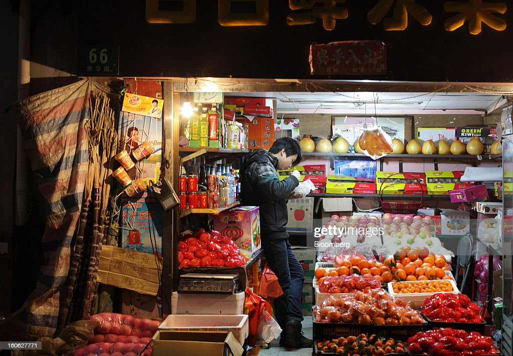 A vendor eats his dinner inside fruit stall in Shanghai, China, on Friday, Feb. 1, 2013. China's services industries grew at the fastest pace since August as gains in retailing and construction aid government efforts to drive a recovery in the world's second-biggest economy. Photographer: Tomohiro Ohsumi/Bloomberg via Getty Images