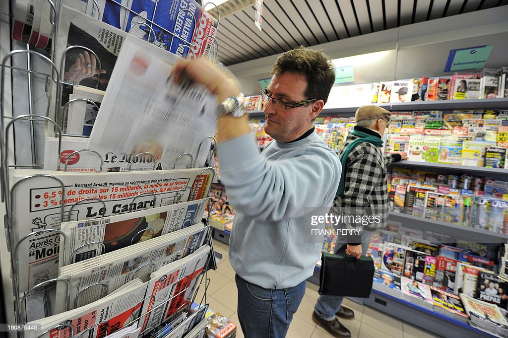 A vendor fills a newspapers stand in a bookshop on february 7, 2013 in Nantes, western France.